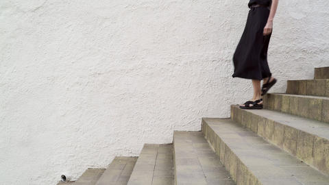 Girl with long hair, black dress and black hat walking down the stairs against a Live Action