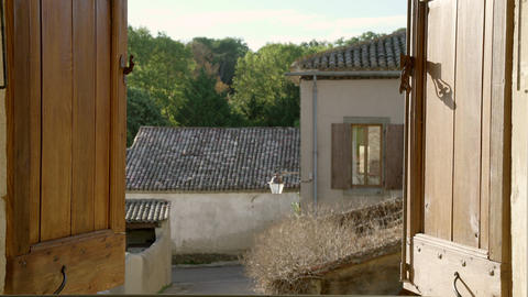 A girl with long hair opens a window overlooking an old village. Idyllic Live Action