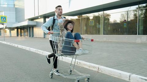 Slow motion of joyful couple riding shopping cart in modern city having fun Live Action