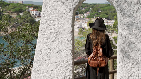 Girl with long hair in black kaftan dress and black hat staying in the white arc Live Action