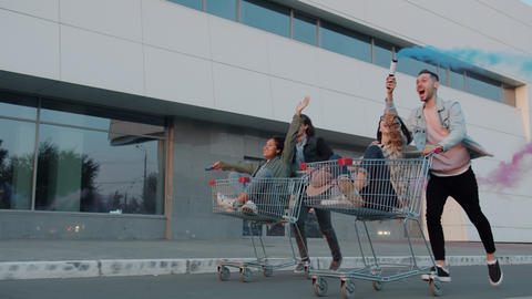 Cheerful youth riding shopping carts in city street holding smoke flares Live Action