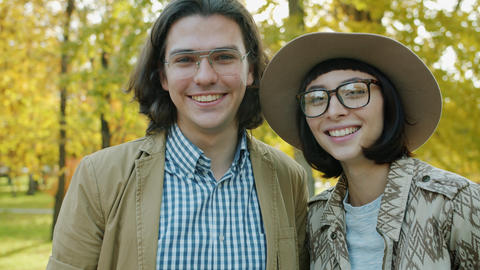 Happy youth girl and guy smiling looking at camera in urban park feeling joyful Live Action