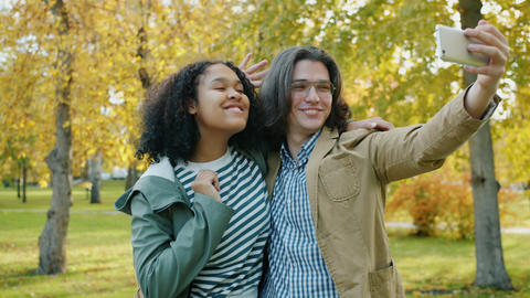 Slow motion of girl and guy taking selfie in park hugging having fun with Live Action