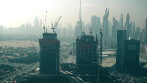 Aerial shot of an urban skyscrapers construction site against Dubai skyline, UAE Live Action