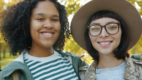 Close-up portrait of attractive ladies Afro-American and Caucasian smiling Live Action