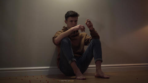 Portrait of addicted Caucasian boy sitting on the floor with syringe. Teenage Live Action