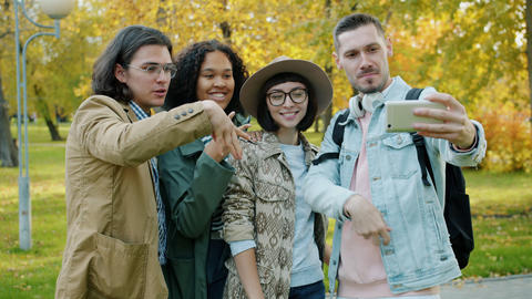 Slow motion of playful youth having fun outdoors taking selfie with smartphone Live Action
