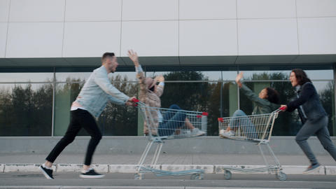 Playful youth young couples running riding shopping carts enjoying leisure time Live Action