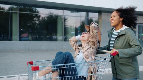 Mixed race girl running pushing shopping cart with female friend having fun Live Action
