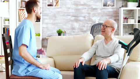 Retired pensioner in nursing home talking with a male nurse Live Action