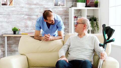 Elderly man having a conversation with a male nurse in cozy nursing home Live Action