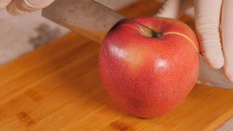 Cutting an Apple on a wooden Board. The fruit falls apart. The slices fall apart Live Action