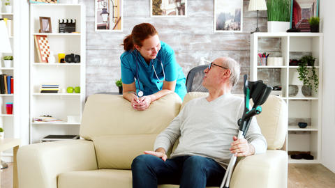 Retired man in nursing home talking with a nurse Live Action