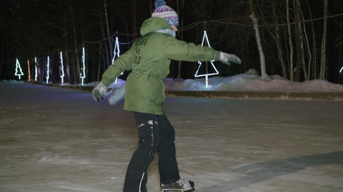 Teenager boy skating on skates on night ice rink in winter park. Cheerful boy Live Action