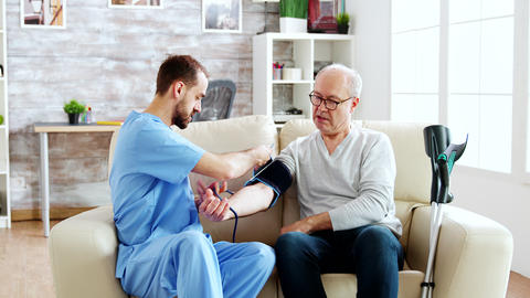 Male nurse measuring blood pressure of a man pensioner Live Action