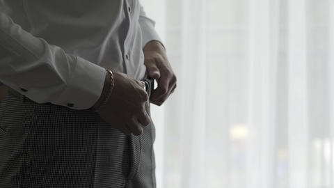 Male businessman fastens a belt on his pants Live Action
