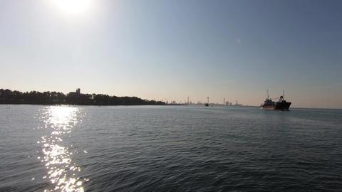 Seaside landscape。Cargo ship with sunshine Live Action