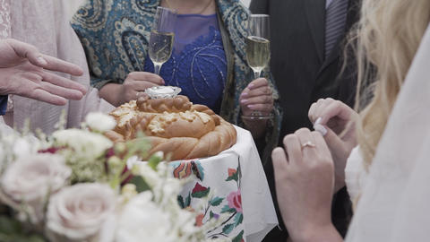 Newlyweds breaking traditional wedding bread at celebration Live Action
