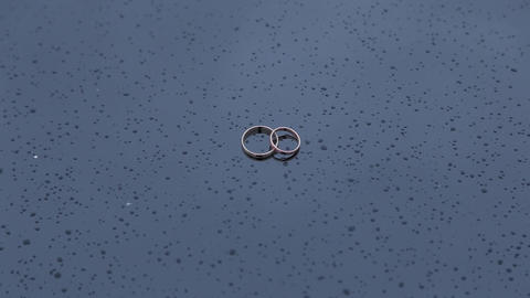 Beautiful golden wedding rings on wet surface with water drops Live Action