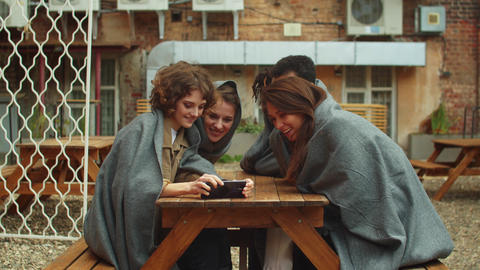 Multicultural friends in blankets sit outside, girl take a group photo Live Action