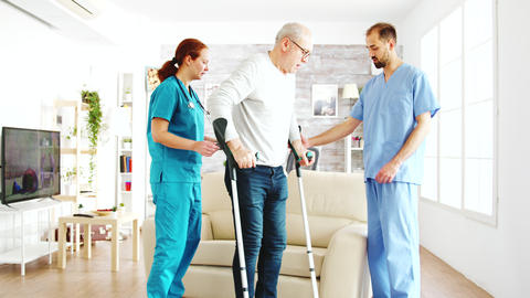 Two nurses hekping an old disabled man with crutches to walk in his room Live Action