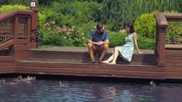 Pair sit on a wooden bridge and looking at the lake where ducks swim Footage