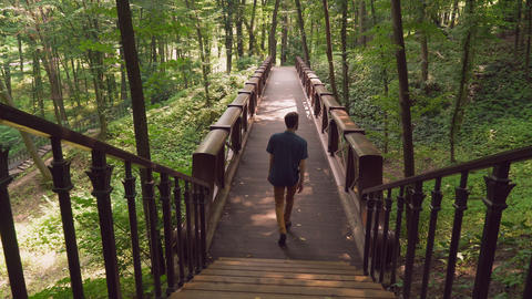 A guy coming down the stairs, walking on a wooden bridgework in the forester Footage