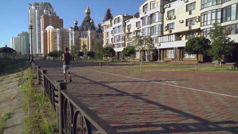 Runner training at the open air. On the backgroung orthodox temple Footage