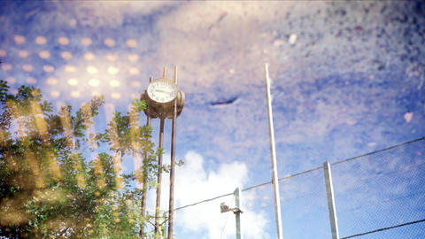 Clock of backstop and park of baseball field to be reflected in puddle Footage