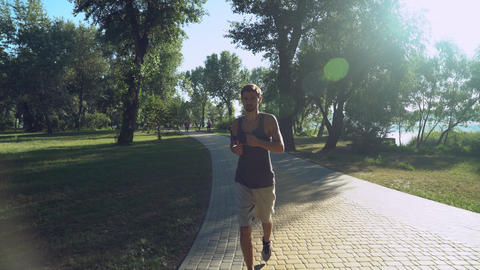 A young guy with headphones running back in the park, where walking and running  Footage