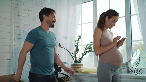 Husband giving yellow flowers to surprised pregnant wife at home Live Action