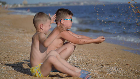 Rest on the sea with children. The boys throw up a shell with sand. Children's Live Action