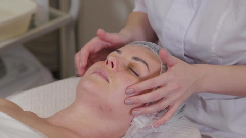 Professional beautician woman doing facial massage to patient Live Action