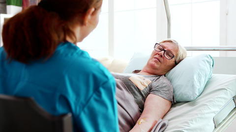 In nursing home old sick lady lying in bed talks with a female nurse Live Action