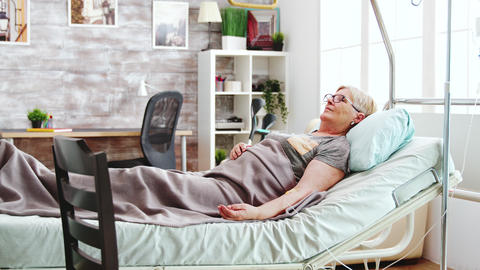 In bright retirement home old lady lying in hospital bed talks with a female Live Action