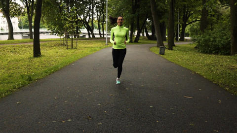 Sport woman running in park exercising outdoors Live Action