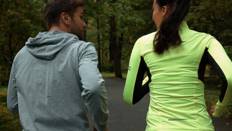 Woman and man communicating and smiling during morning jog. They running at the Live Action