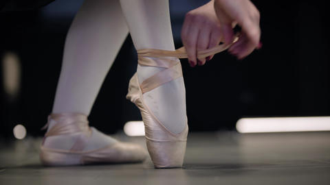 Close-up feet of Caucasian female ballet dancer tying pointe shoes. Graceful Live Action