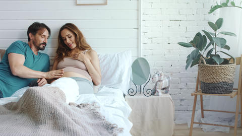 Smiling husband stroking pregnant belly of wife. Pregnant couple huggins in bed Live Action