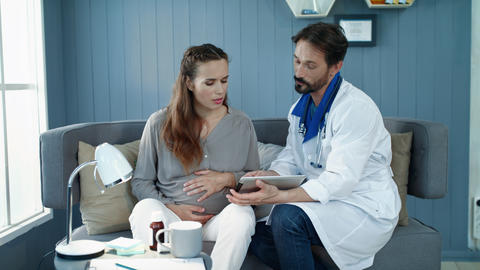 Closeup doctor showing test results in office. Pregnant woman looking tablet Live Action