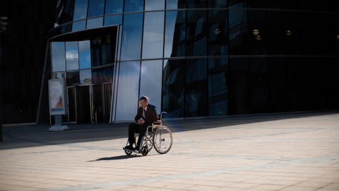 Sad handsome entrepreneur man in wheelchair whith indifferent crowd Live Action
