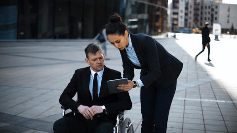 Invalid boss businessman in wheelchair an his lady secretary work with Digital Live Action