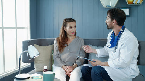Beautiful pregnant woman talking with doctor on couch in cabinet Live Action