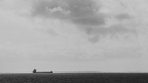 Big ship sailing on the sea on the horizon. Dramatic sea. Strong wind. Clouds Live Action