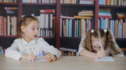 Schoolgirls writing from cheat sheet on school exam at bookcase background. Two Live Action