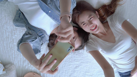 top view video of Two pretty Asian friends are playing cell phones on the bed, the concept of Live Action