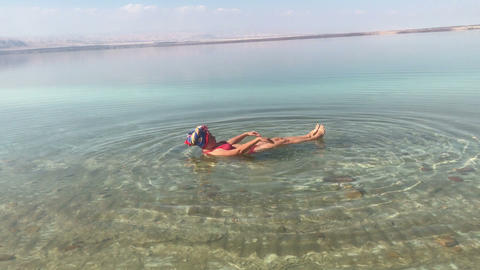 woman swimming in a dead sea, funny, laying on back, travel shots on mobile Live Action