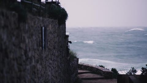 Storm waves hit the rocks in a small bay with a small coastal village. Stone Live Action