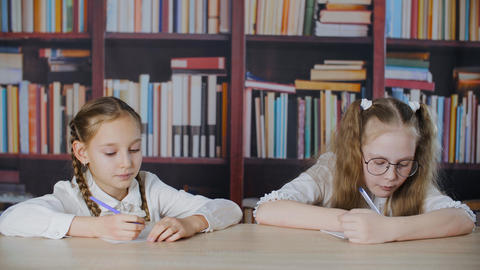 Schoolgirl copying solution from classmate at exam in school on bookcase Live Action