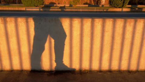 Walking man shadow on the concrete fence. Yellow sunlight and contrasting Live Action